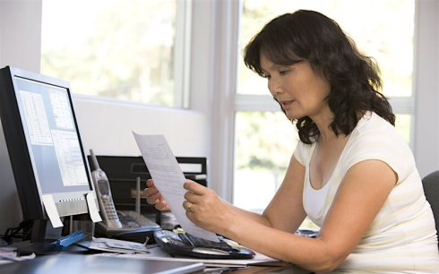 p40b-older-woman-reading-letter-near-computer